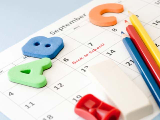 ABC titles, pencils, an eraser, and a sharpener laying on a school calendar