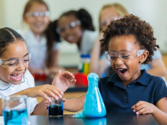 Two young students laughing watching a beaker overflow during a science expeeriment