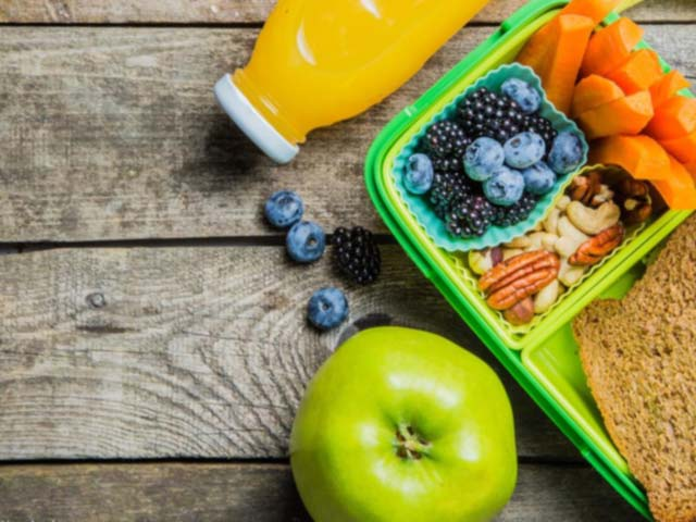 Plastic lunch box with fruits, nuts, carrots, juice, and apple, and sandwich on a wooden table