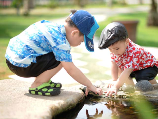 Two young boys playing together, reaching into a pond