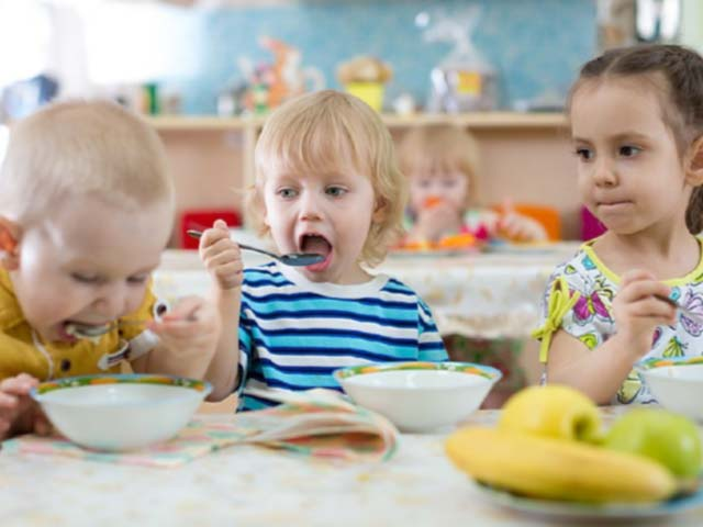 Two young boys and a little girl eating their lunch together